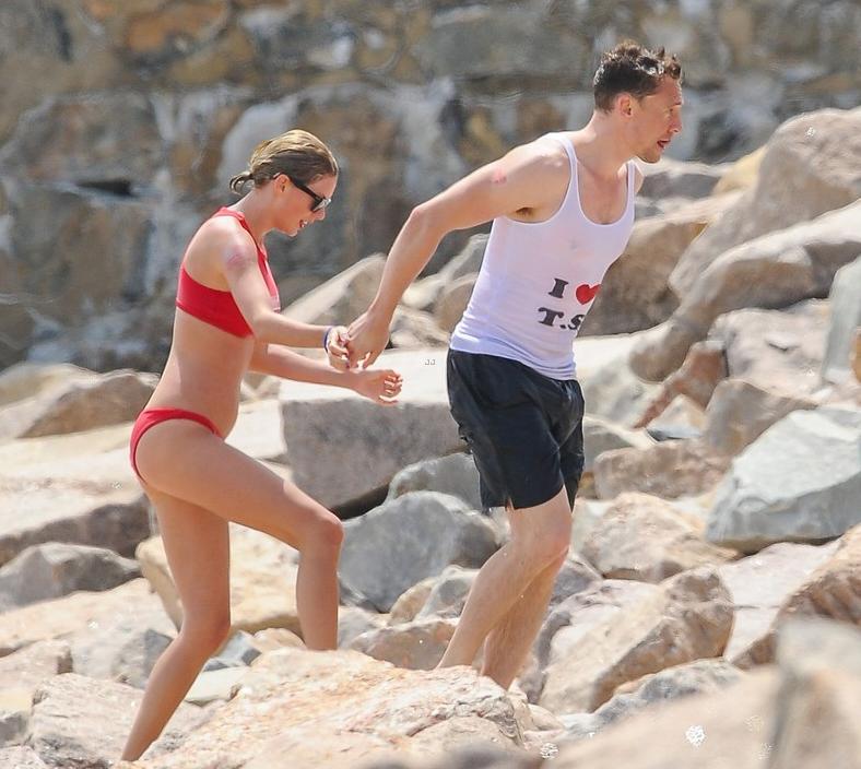 Tom Hiddleston med partnern Taylor Swift går på klippor på en strand